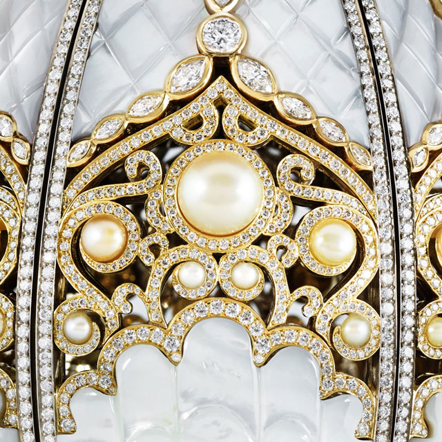 Close up view of closed Faberge pearl egg, with pearls, white diamonds, and gold setting