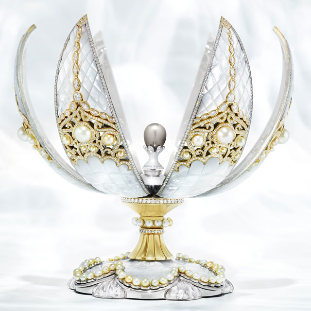 Faberge pearl egg in an open-state, with multiple pearls, mother of pearl exterior, white dimaonds, and jewelled base