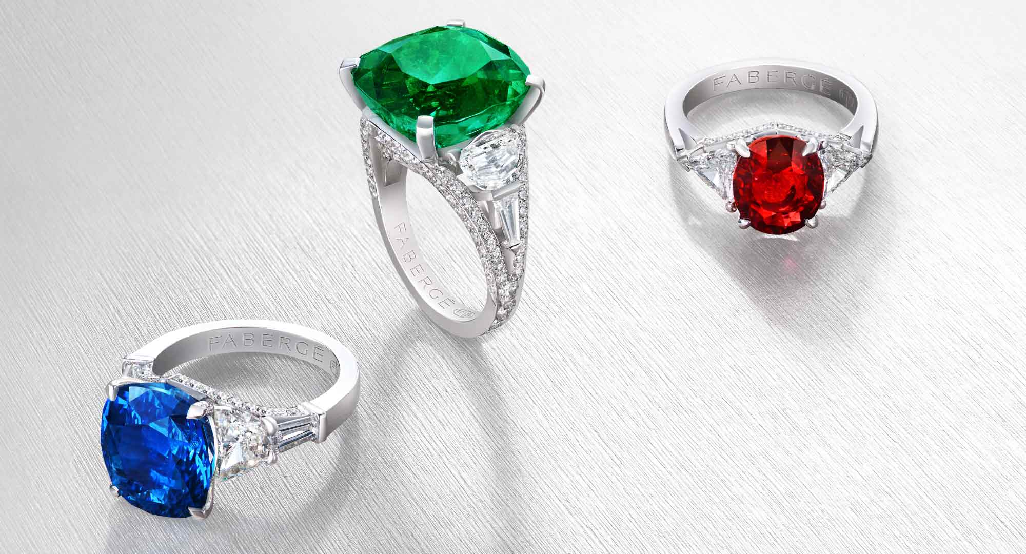 Three gemstone rings from the three colours of love collection: blue sapphire and white diamonds ring, green emerald and white diamonds ring, red ruby and white diamonds ring.