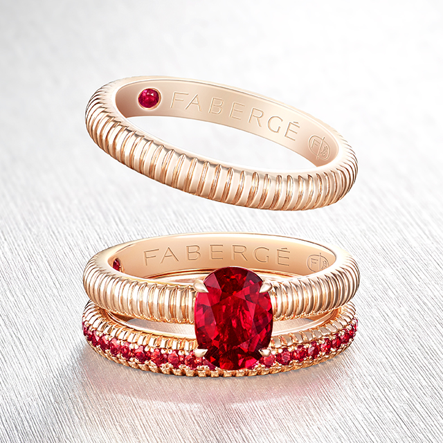 Three stackable rings from the three colours of love collection. One fluted rose gold ring, one red ruby centre stone fluted rose gold ring, one fluted rose gold with rubies ring.