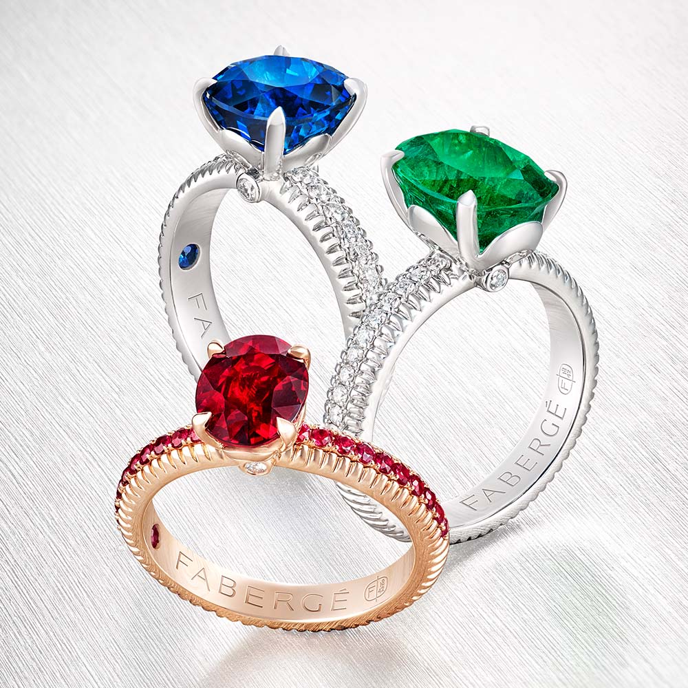 Close up view of three rings from the three colours of love collection. One blue sapphire and white diamonds ring, one red ruby and rose gold ring, one green emerald and white diamonds ring.