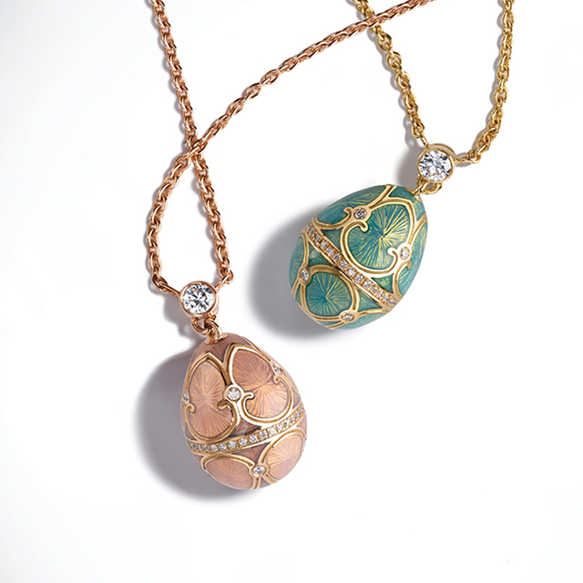 Two Fabergé egg pendants on gold chains from the heritage collection. One with pink guilloche enamel, white diamonds and yellow gold. One with turquoise guilloche enamel, white diamonds and yellow gold.