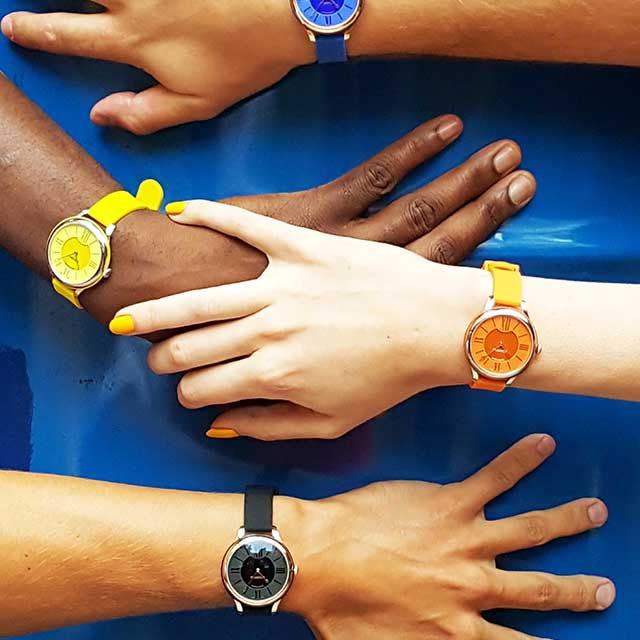 Four timepieces from the Fabergé Flirt Collection being worn on four wrists, including one black watch, one orange watch, one yellow watch, one blue watch.