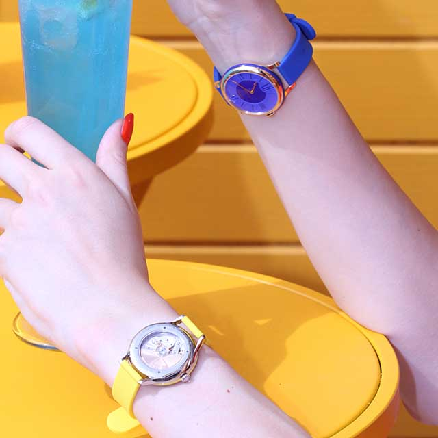 Woman wearing two timepieces from the Fabergé Flirt Collection. One yellow timepiece on left wrist, one blue timepiece on right wrist.