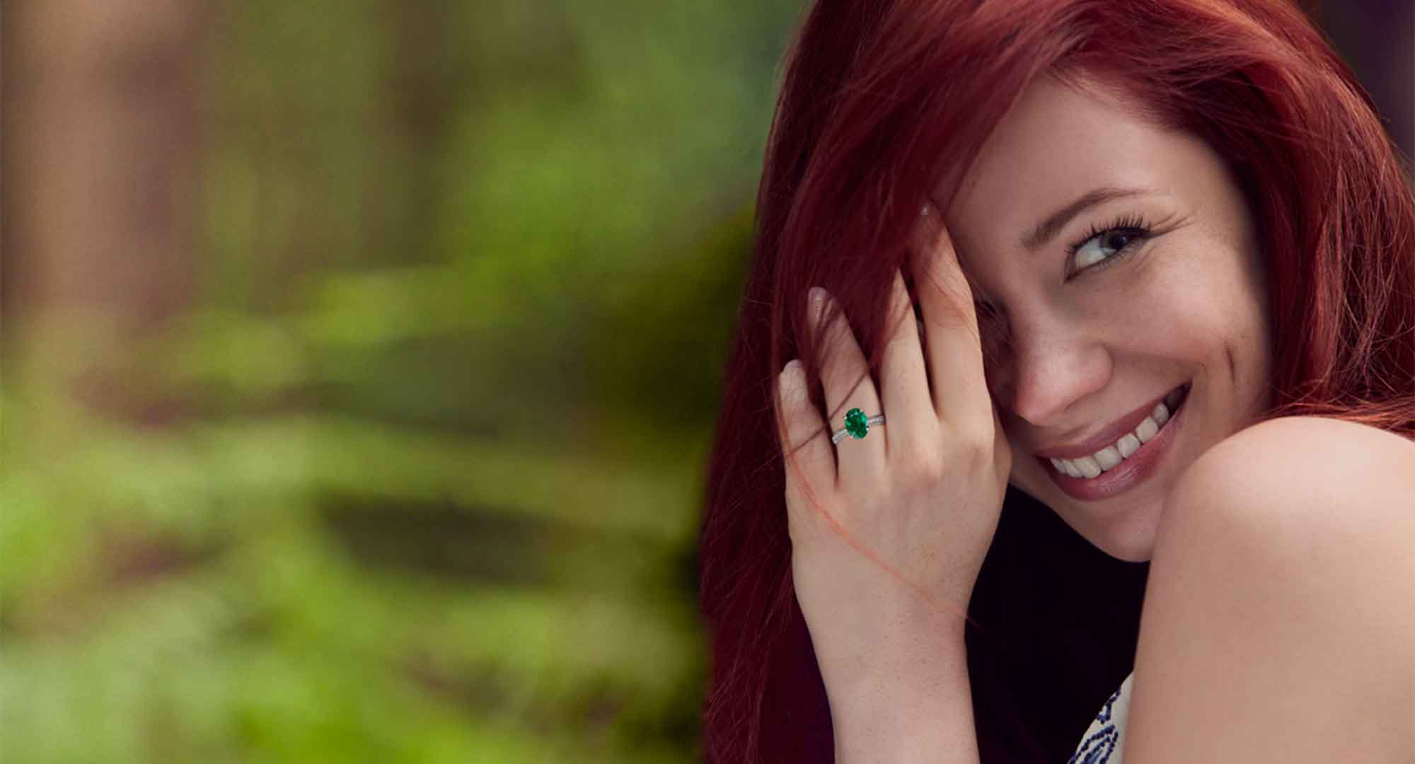 Woman wearing a Fabergé green emerald engagement ring from the three colours of love collection