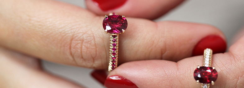 Close up view of a lady's hands with two Fabergé ruby engagement rings