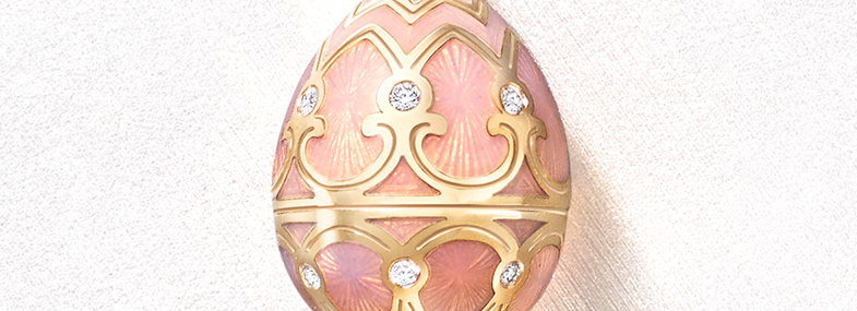 Close up view of a Fabergé egg pendant with pink guilloche enamel, white diamonds and yellow gold from the heritage collection.