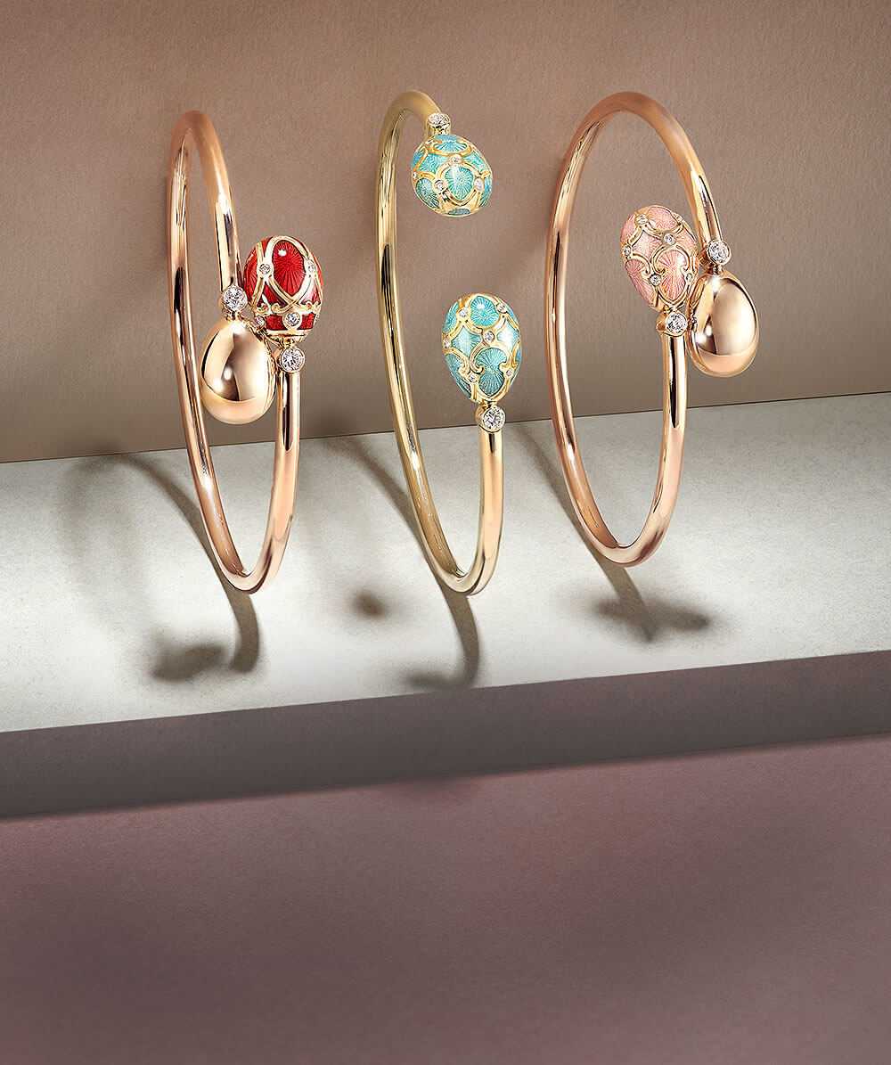 Three Fabergé open-set bangles on a woman's wrist