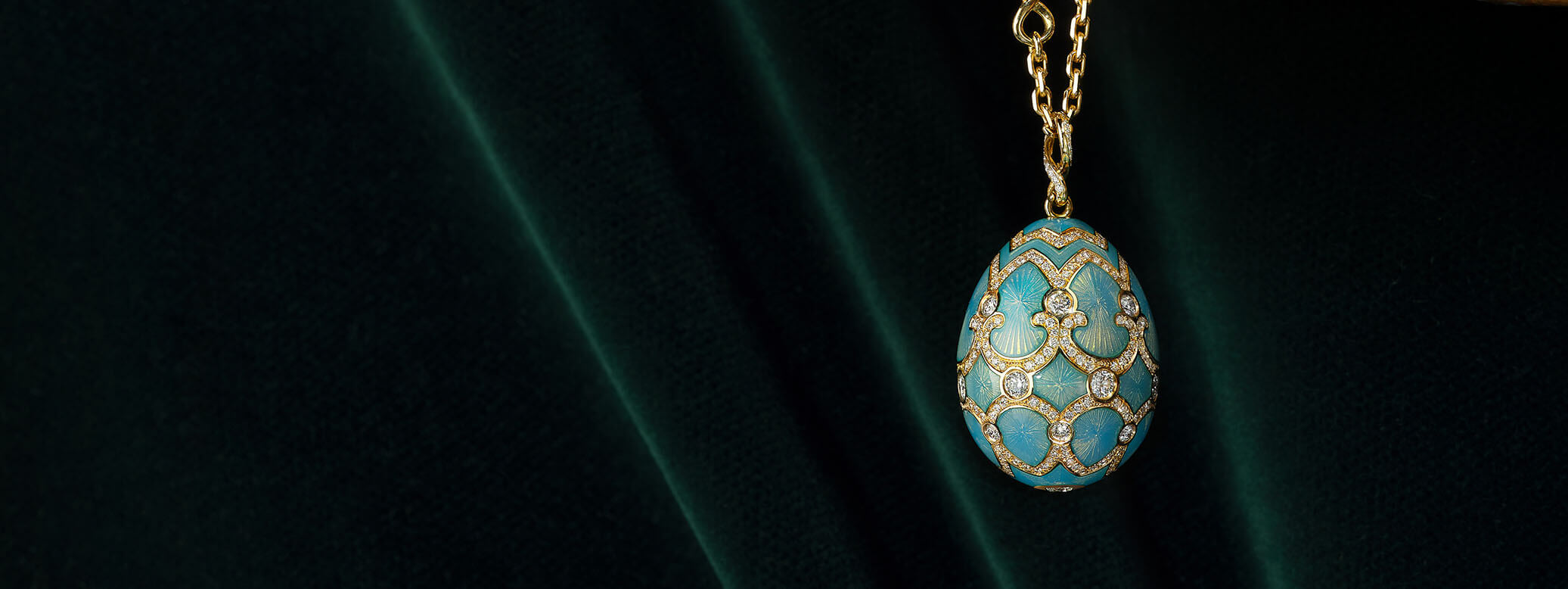 Close up view of Fabergé egg pendant with white diamonds and green emeralds