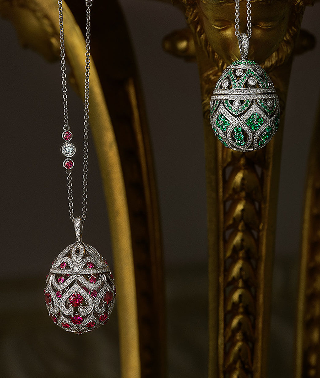 Close up view of two Fabergé egg pendants. Pendant on left: Turquoise enamel with white diamonds and yellow gold. Pendant on right: Pink enamel with white diamonds and yellow gold.