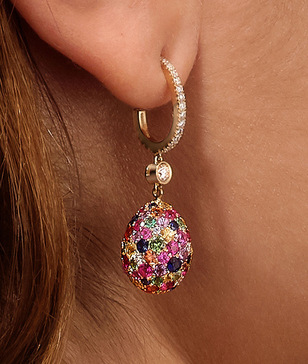 Close up view of two Fabergé egg pendant earrings