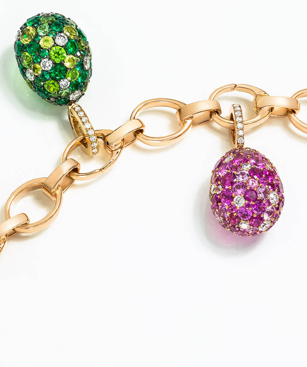 Three Fabergé egg charms hanging on a gold bracelet. Egg charm on left: Treillage diamond rose gold charm. Middle egg charm: Rococo rose enamel rose gold charm. Egg charm on right: Emotion purple charm.