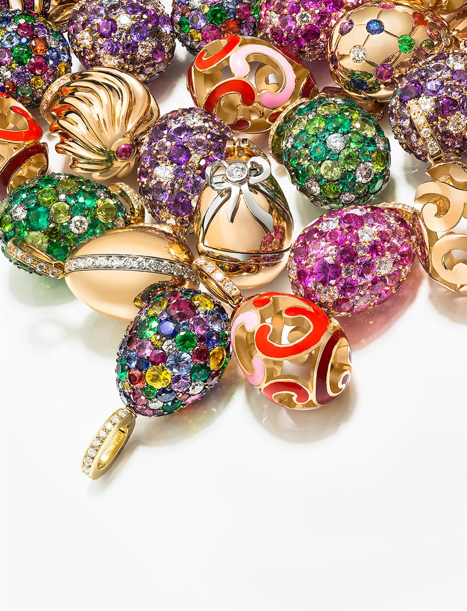 Woman's hands holding an open bracelet with multiple Fabergé egg charms attached